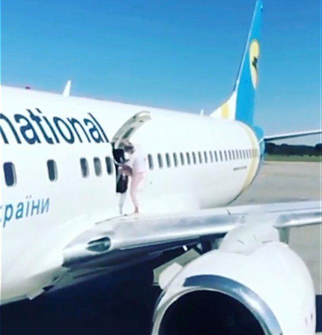La mujer abrió la puerta de un avión y salió a caminar por el ala porque tenía calor.